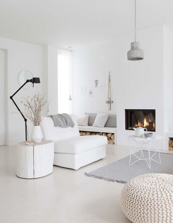 a minimalist Nrodic living room in white, off-whites and greys plus a cozy built-in fireplace