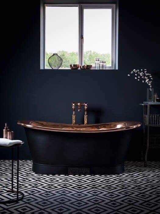 a moody bathroom with a fantastic black bathtub with a copper surface inside is a gorgeous idea