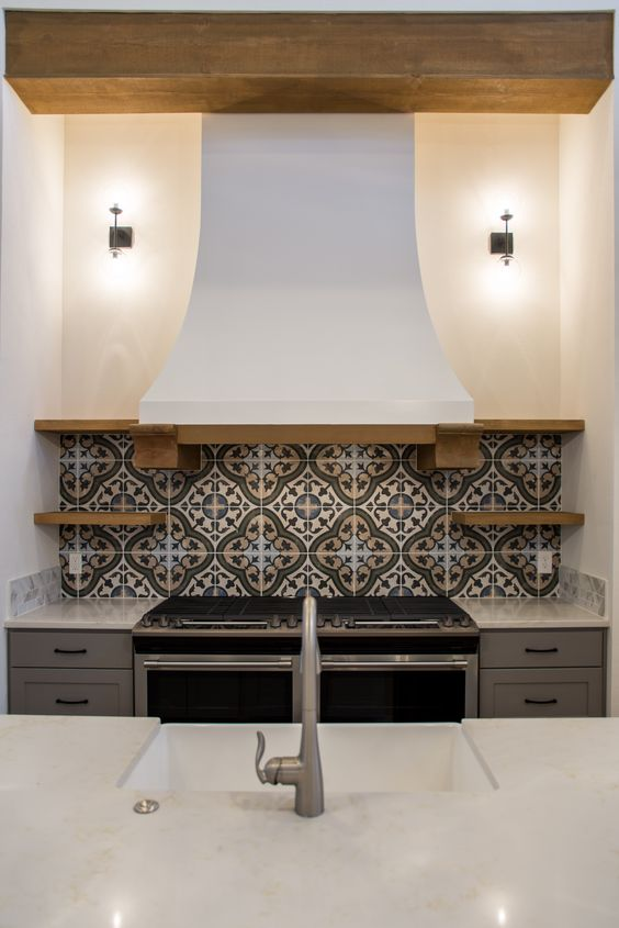 a mosaic tile backsplash and a vintage kitchen hood bring Mediterranean vibes to the space