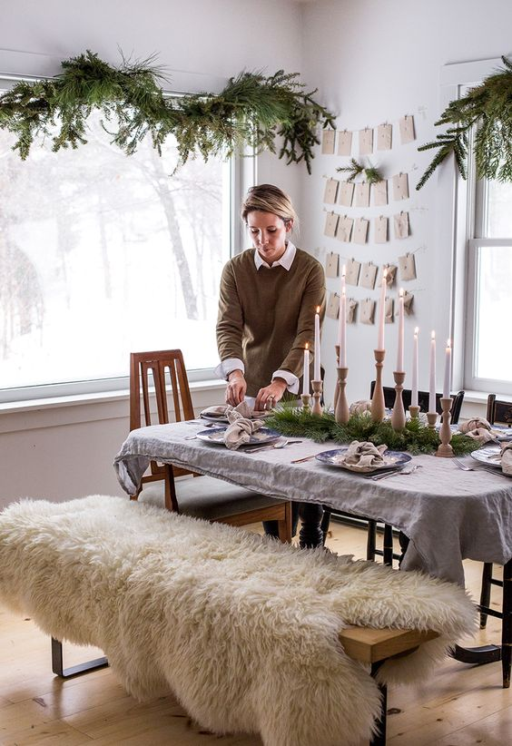 natural evergreen garlands and a matching table runner plus wooden candle holders are great for a hygge space
