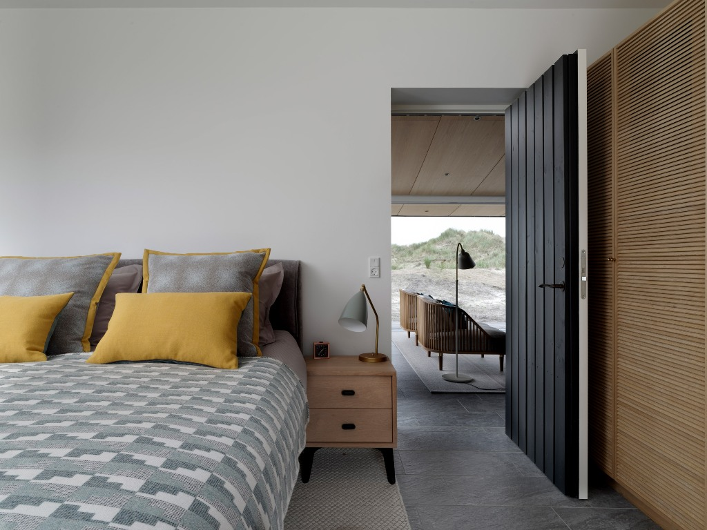 The bedroom is done with a comfy bed and some storage items clad with wood or plywood