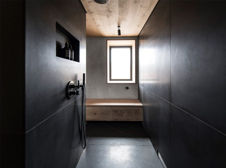 The master bathroom is done with black tiles and concrete and wood to tie it up with other spaces