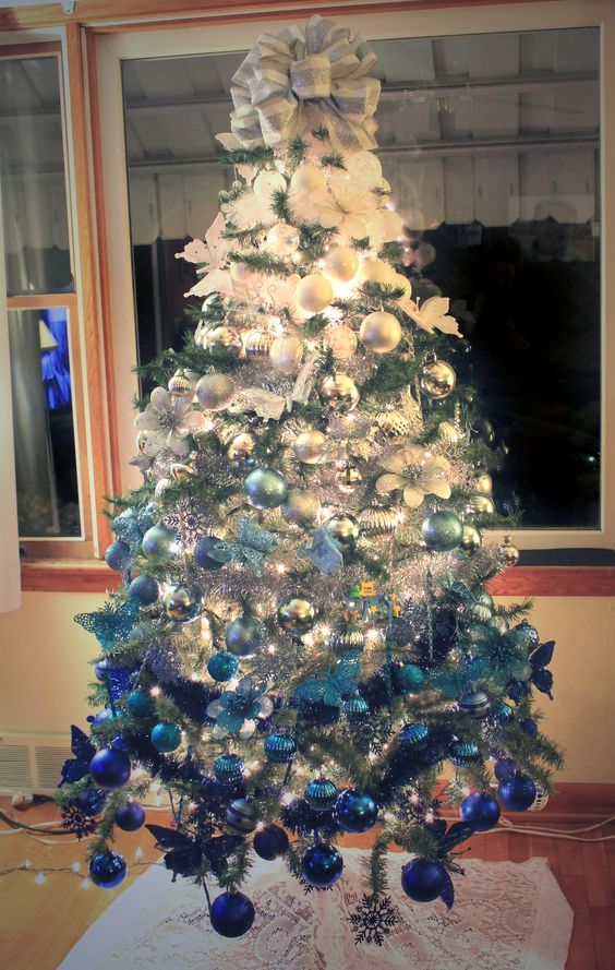 a chic white to silver and blue ombre Christmas tree with lights, a large bow and some glitter looks frozen
