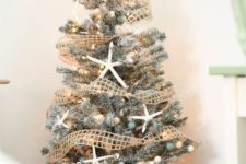 07 a flocked Christmas tree decorated with star fish, nets and beach-colored pompoms and lights