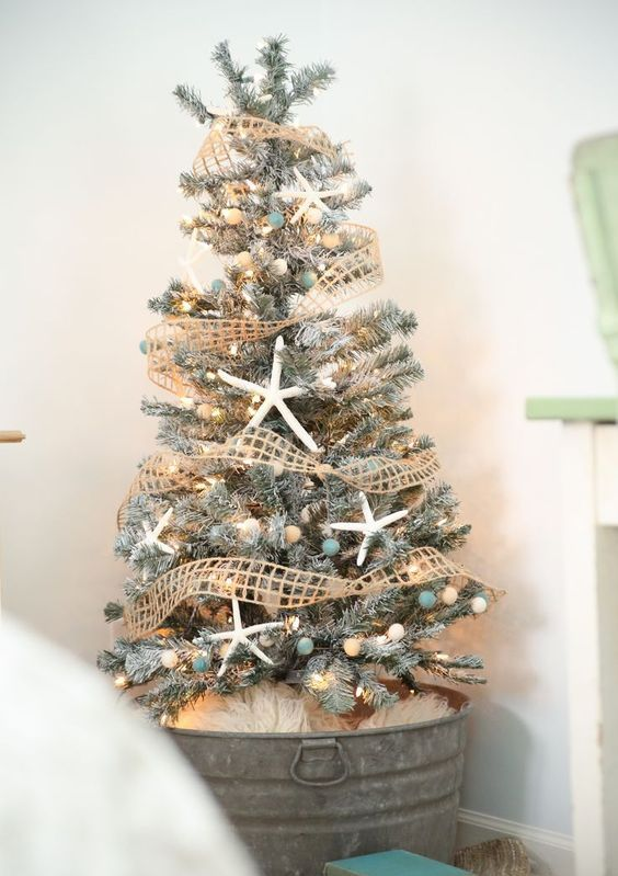 a flocked Christmas tree decorated with star fish, nets and beach-colored pompoms and lights