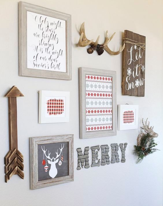 a holiday gallery wall with signs, letters, artworks, a fake deer head and an arrow for Christmas