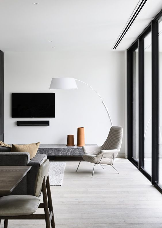 a minimalist living room with quirky and stylish furniture and much natural light comfing through a glazed wall