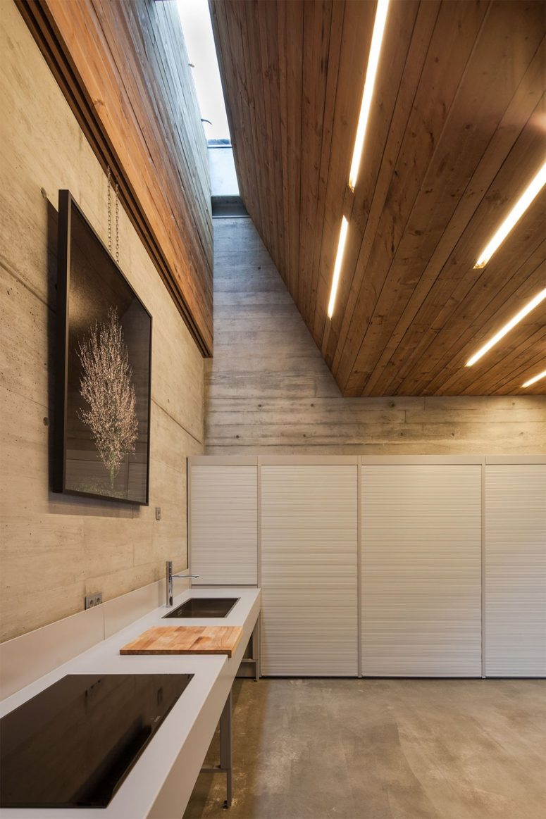 The kitchen is done with a large concrete kitchen island by the wall and closed cabinets with everythign necessary