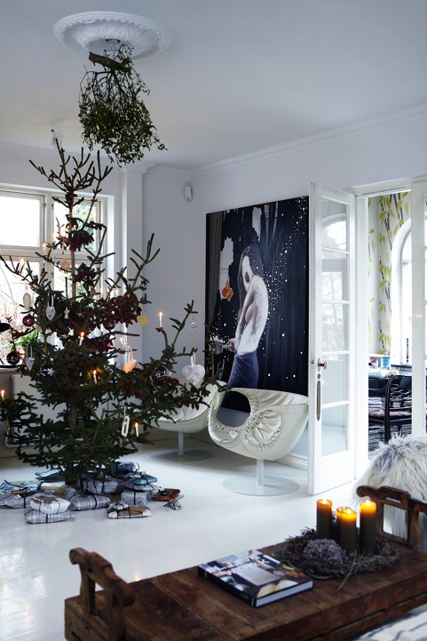 The living room is done with an oversized artwork, very catchy chairs and a large Christmas tree with ornaments and hanging greenery