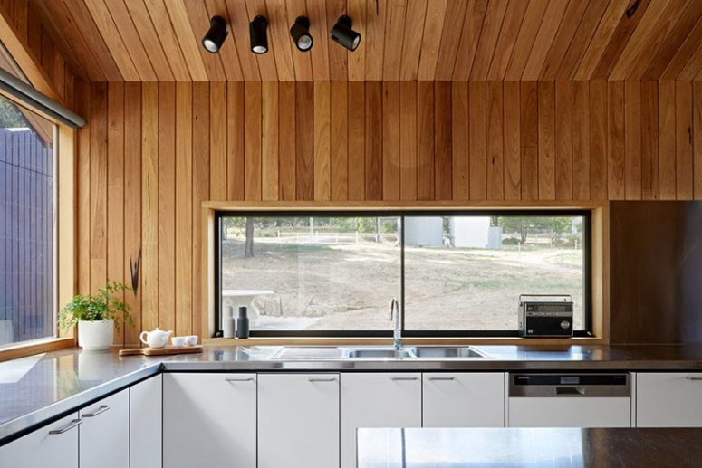 There are windows instead of backsplashes that let much light in and allow enjoying the views while cooking