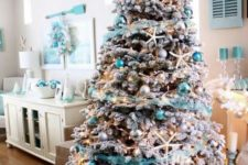 08 a flocked Christmas tree with star fish, silver and turquoise ornaments and turquoise garlands