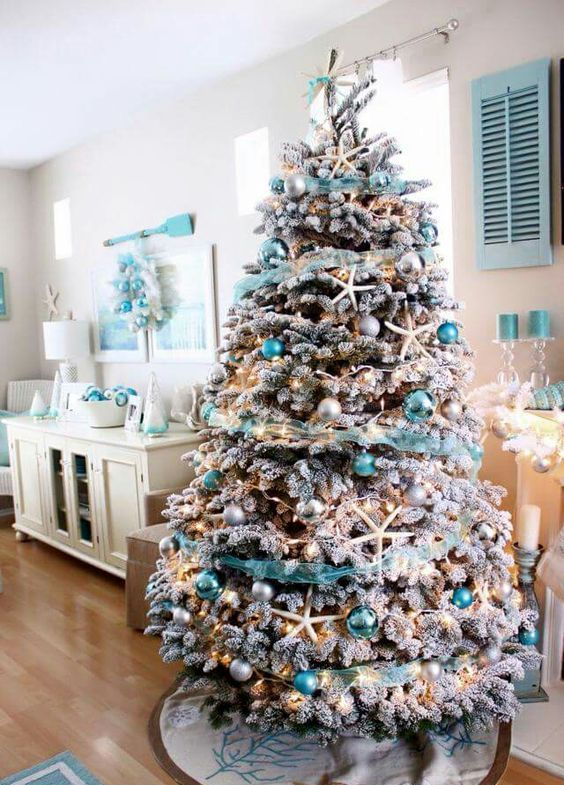 a flocked Christmas tree with star fish, silver and turquoise ornaments and turquoise garlands