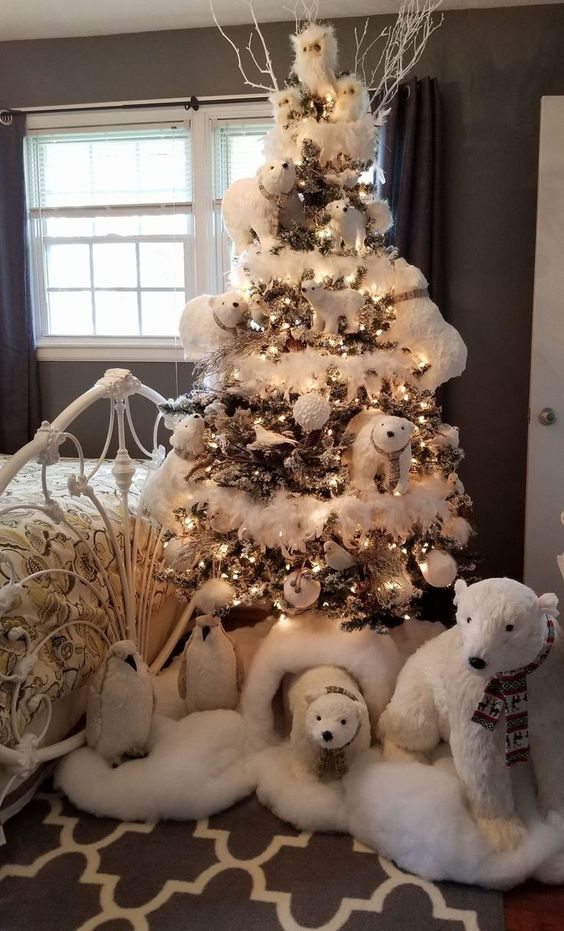 a kid's Christmas tree decorated with polar bears, white snowy ornaments, lights and even penguins is a whimsy idea