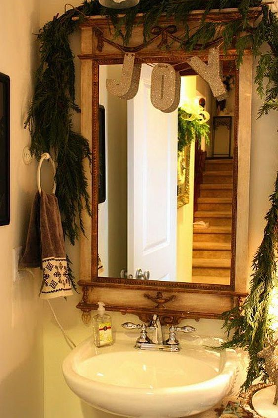 a lush evergreen garland to cover the mirror and a glitter letter garland for a holiday feel