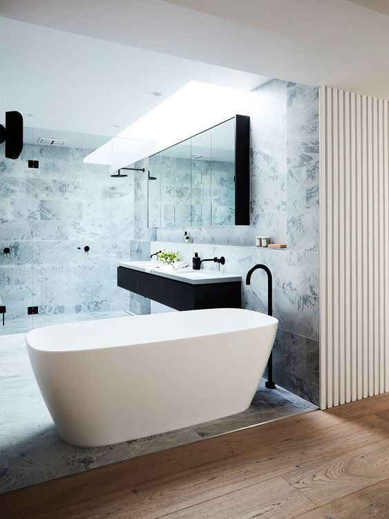a minimalist bathroom with a comfy free-standing bathtub and marble tiles for a chic look