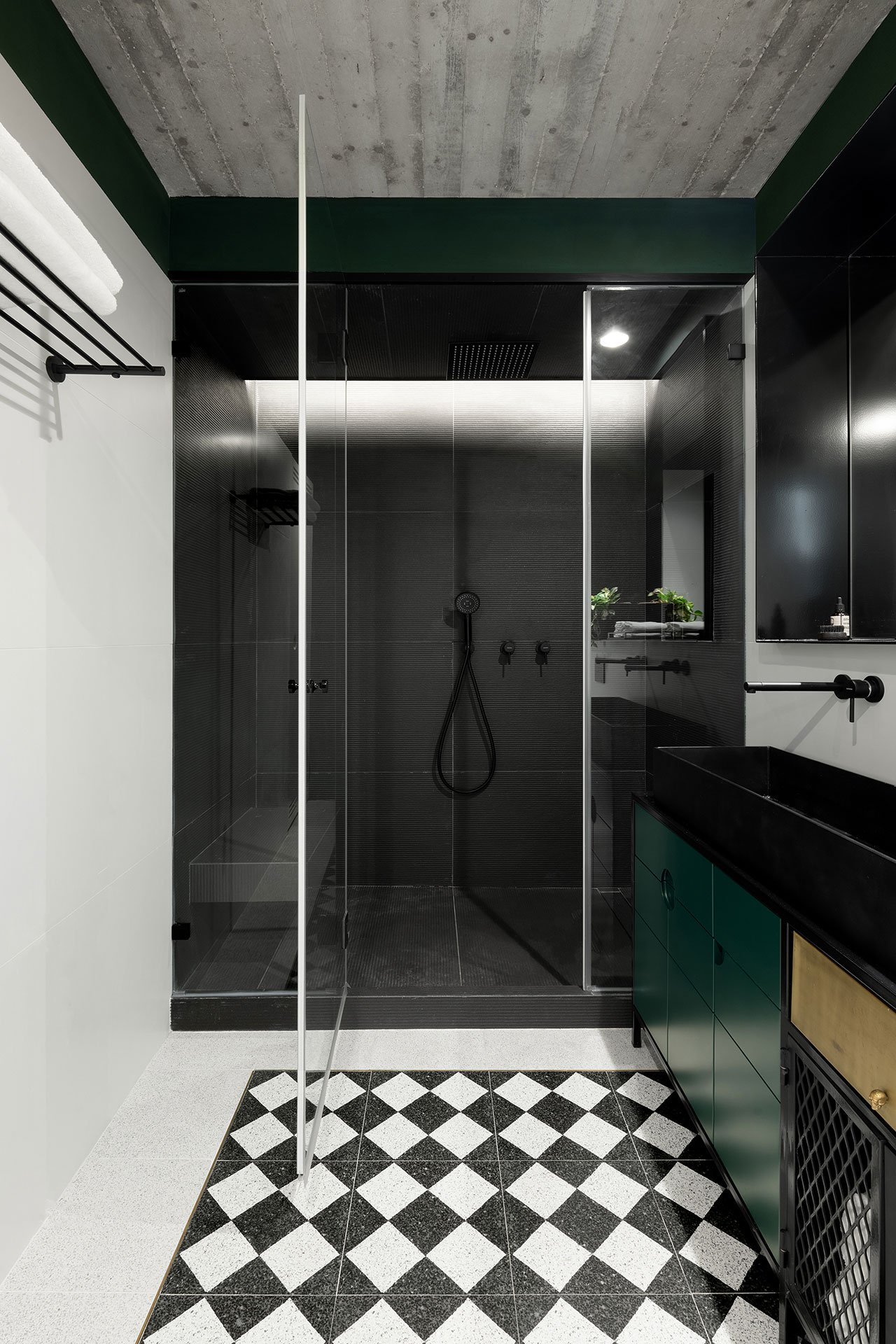 The bathroom is done in black, white and emerald, with geometric patterns to tie the spaces