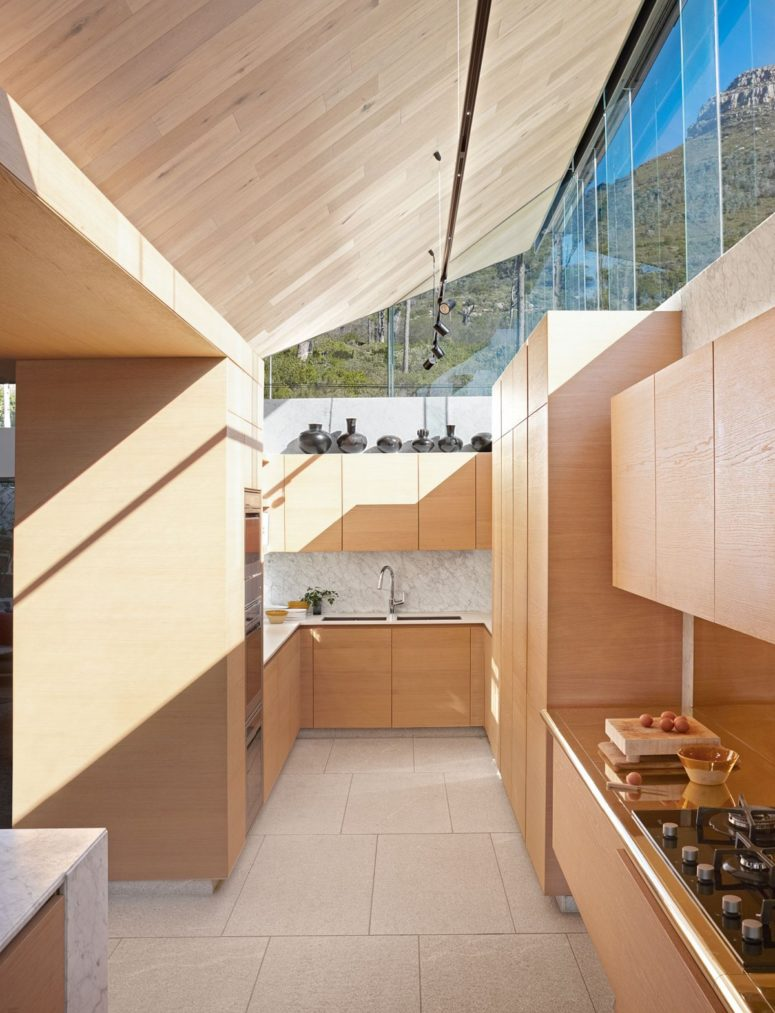 The kitchen is done with light-colored wooden cabinets and stone