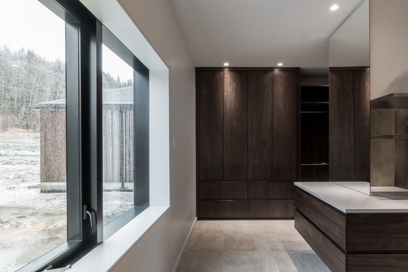 The storage is hidden inside various closed units in dark wood, which makes the spaces decluttered