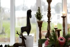 09 There's a windowsill display with wooden candle holders, gifts, deer figurines and lush blooms and greenery in a vase