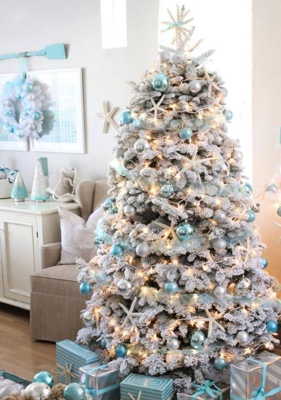 a gorgeous flocked coastal Christmas tree with blue and pearly ornaments plus lights and star fish