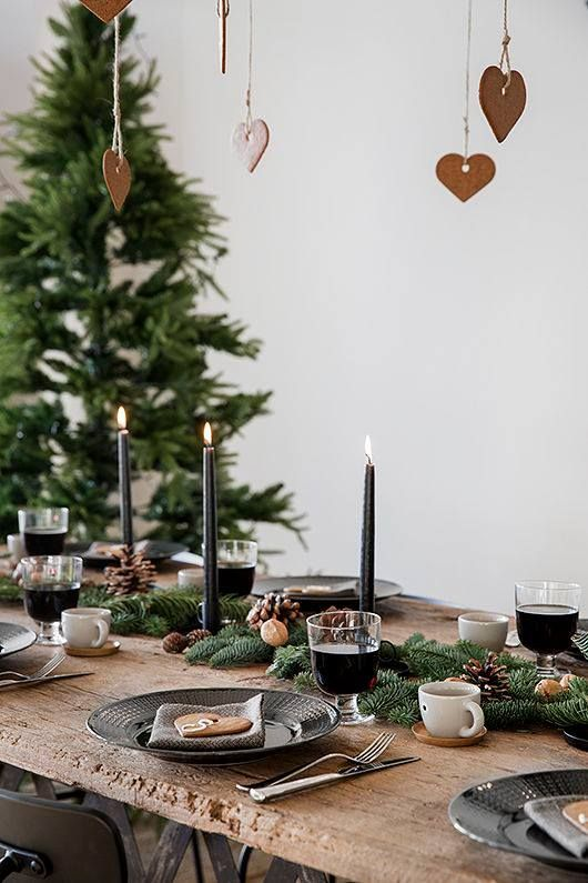 a hygge-inspired Christmas table setting with an evergreen garland, pinecones, nuts and black candles