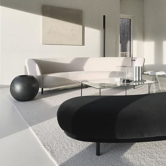 a minimal living room with black and white sofas, much natural light and glass coffee tables