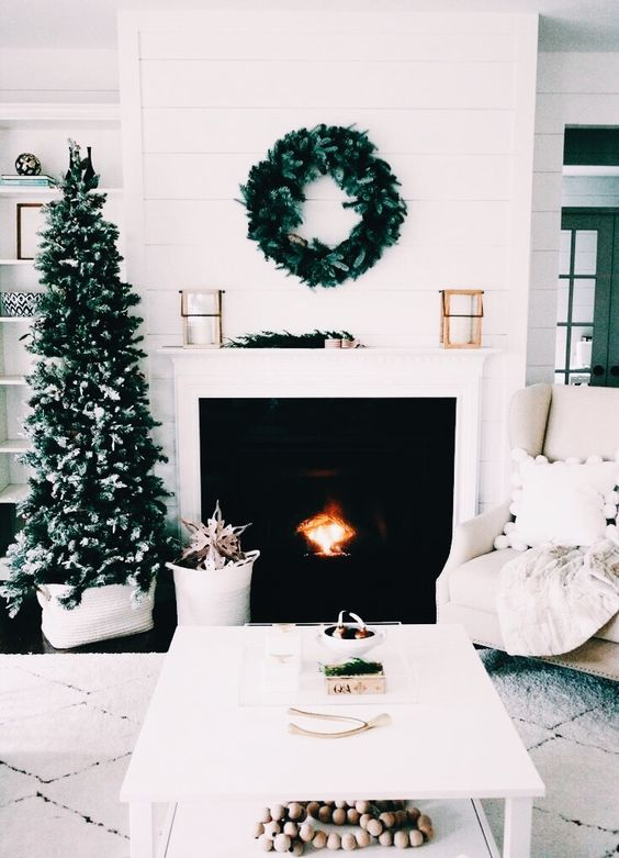 a neutral living room decorated with evergreens - a wreath and a plain Christmas tree for a laconic look