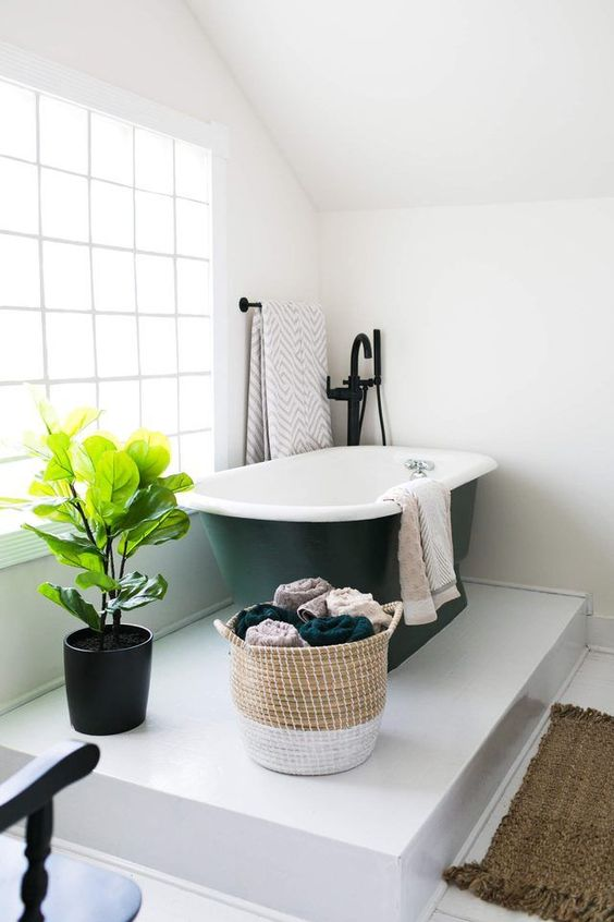 a platform bathing space with a black bathtub in the corner and a potted plant looks very cozy and comfy