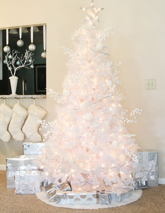 a pure white Christmas tree decorated with lights, branches, ornaments and lights seems very airy and beautiful