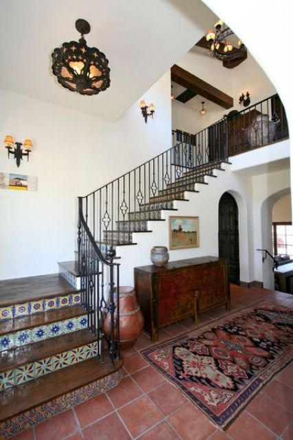 colorful mosaic tiles on the stairs and a bright print rug plus a vintage dresser for a Mediterranean entryway