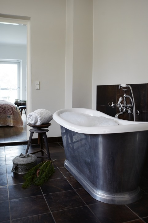 The bathroom is done in black and white, with some vintage stuff and a large galvanized bathtub