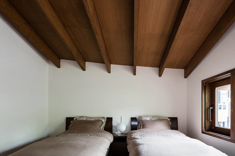 The guest bedroom is a shared one, its laconic decor features two beds and an attic roof