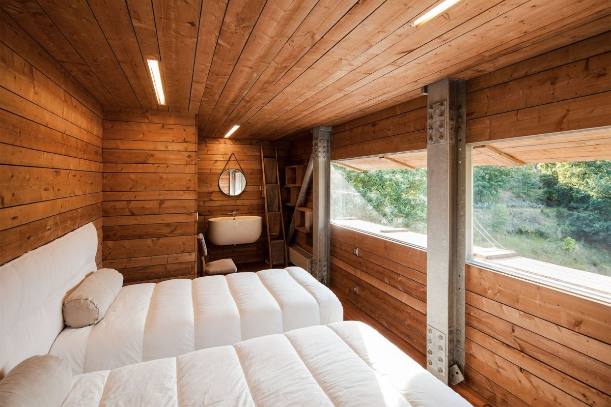 The guest bedroom is shared, there's also a mudroom right here, the space is clad with wood and there are metal pillars