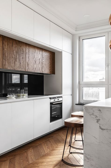 a minimalist kitchen done in white, with a marble kitchen island and rich-colored wooden cabinets