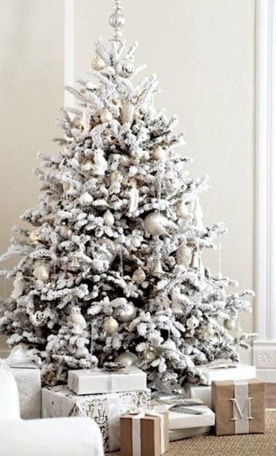 a snowy Christmas tree with pearly and silver ornaments, snowy branches and a silver topper