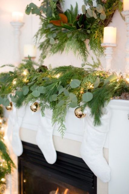 an evergreen wreath and a matching garland with lights and gold Christmas ornaments hanging down