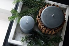 10 candles in soft grey covered with cinnamon sticks and displayed with evergreens are veyr hygge like