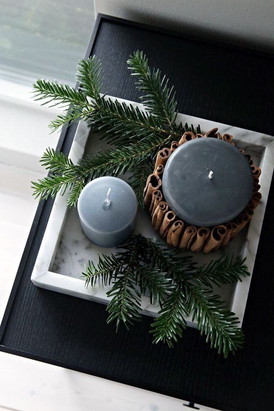 candles in soft grey covered with cinnamon sticks and displayed with evergreens are veyr hygge like