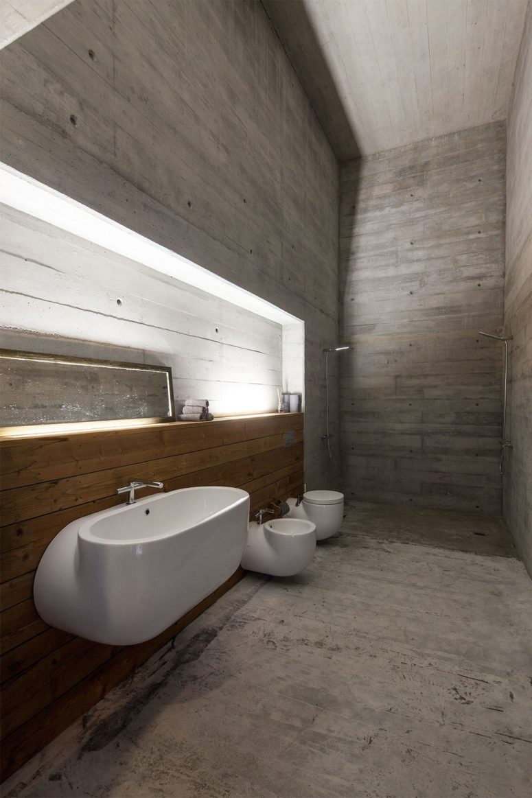 The bathroom is very spacious, it's done with concrete and wood and there's a shower in the corner