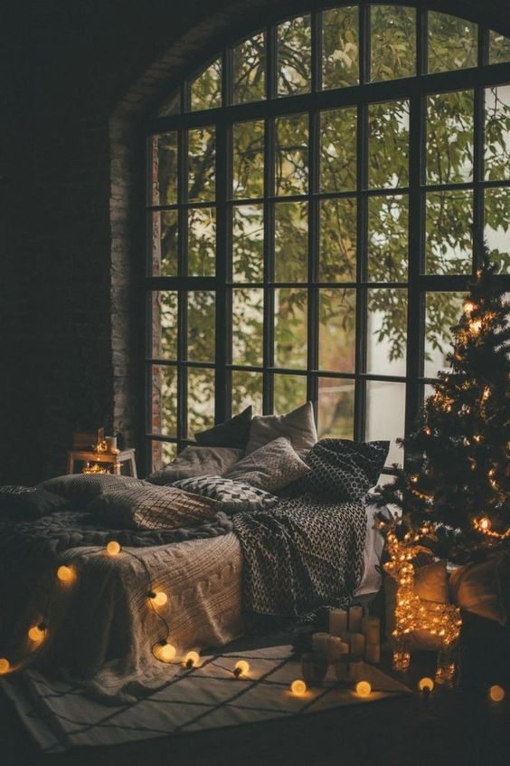 a bedroom lit up only with a Christmas tree with lights and a string of lights for more coziness