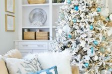 11 a chic flocked Christmas tree with turquoise and blue ornaments, star fish and fake corals, matching pillows