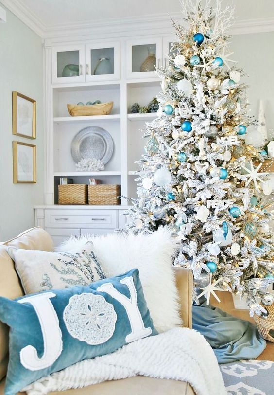 a chic flocked Christmas tree with turquoise and blue ornaments, star fish and fake corals, matching pillows