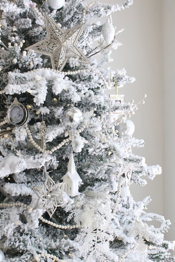 a snowy Christmas tree with star,church and snowflake ornaments and bead garlands looks like a frosted one