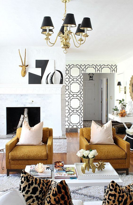 an eclectic living room done in black, gold, white as a cohesive color scheme for decor