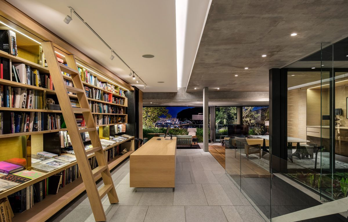 A large and sophisticated home office occupies a section of the middle floor and features an entire wall of bookshelves