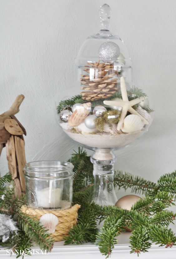 a beach Christmas display of a jar with sand, seashells, star fish, a pinecone and evergreens is a chic idea