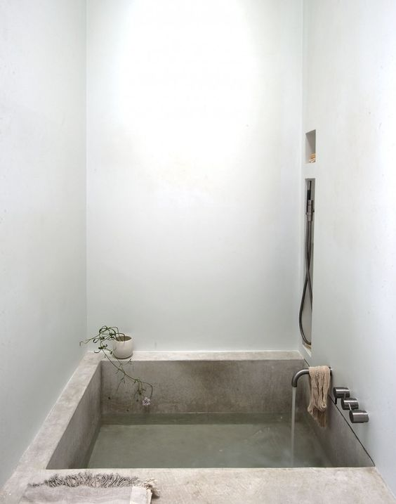 a concrete bathtub is a cool idea to rock in a minimalist bathroom, it's durable and comfortable