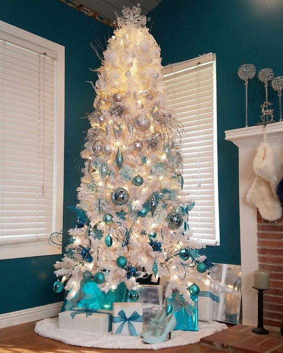 a white Christmas tree with an ombre effect from white and silver to light blue and turquoise plus lights and snowflakes