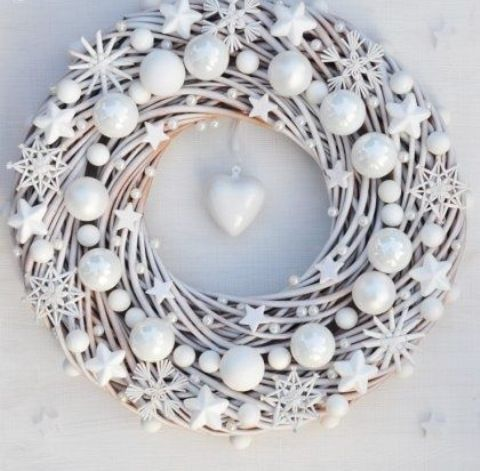 a beautiful white Christmas wreath decorated with stars, snowflakes and beads with a heart in the center