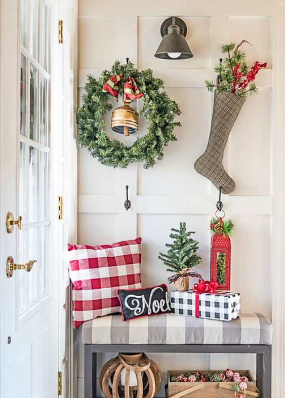 a large greenery wreath with a bell and a plaid stocking with evergreens and berries hanging on hooks